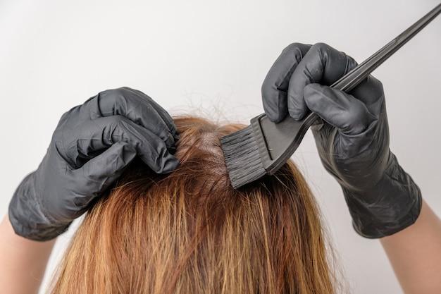 Kobieta farbuje cebulki włosów za pomocą pędzla. farbowanie siwych korzeni włosów o złożonej kolorystyce włosów