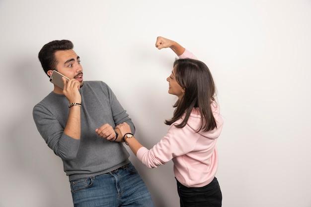 Kobieta figlarnie walcząca ze swoim chłopakiem.