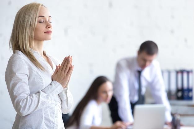 Kobieta firmy medytuje w pracy