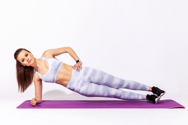 Kobieta fitness ćwicząca jogę, wykonująca ćwiczenie vasisthasana z jedną ręką uniesioną, poza boczną deską