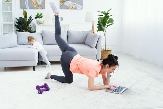 Kobieta fitness, ćwiczenia na podłodze w domu i oglądanie filmów fitness na laptopie. ładna dziewczyna robi trening fitness online.