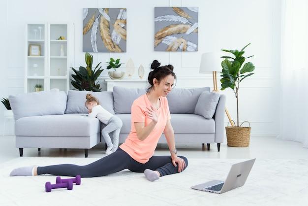 Kobieta fitness, ćwiczenia na podłodze w domu i oglądanie filmów fitness na laptopie. młoda kobieta trener robi szkolenia fitness online dla swoich klientów.