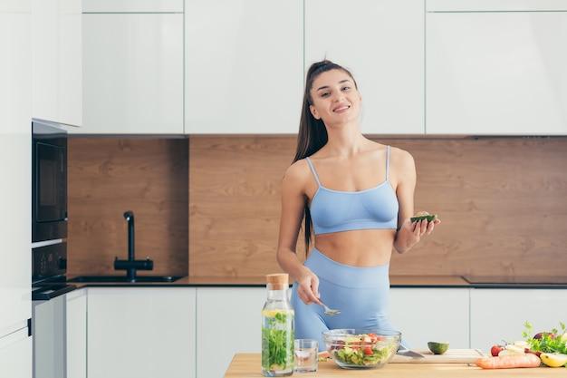 Kobieta fitness przygotowywanie sałatki w domu w kuchni