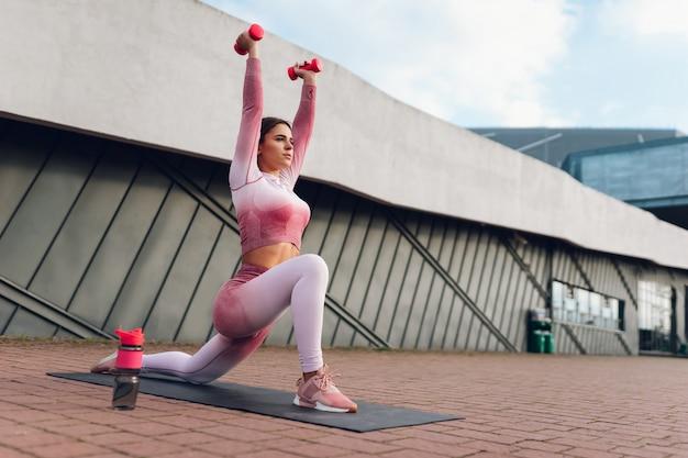 Kobieta fitness robi hantle rzuca się na zewnątrz