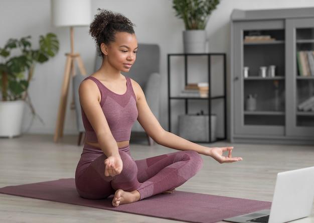 Kobieta fitness robi joga na macie do jogi w domu