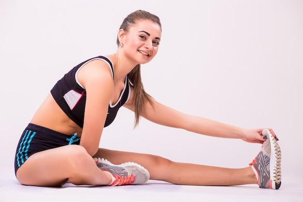 Kobieta fitness robi trening rozciągający. pełna długość strzał młodej kobiety na białym tle.