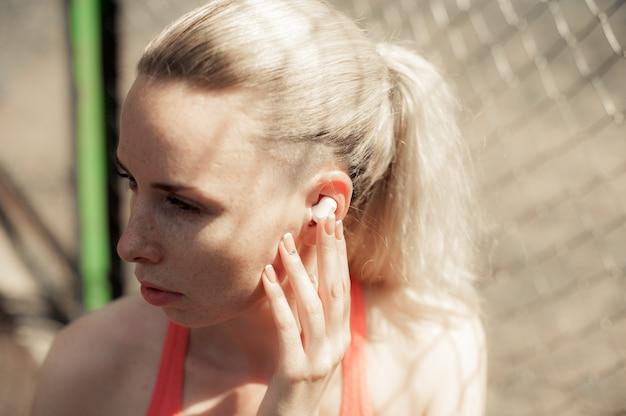 Kobieta fitness słuchanie muzyki w słuchawkach bezprzewodowych, robienie ćwiczeń treningu na ulicy