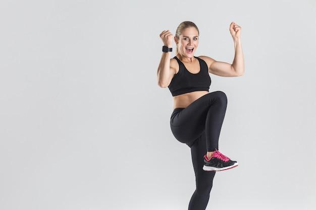 Kobieta fitness sukces i szczęście cieszy się z jej zwycięstwa i uśmiecha się ząb. studio strzał, szare tło