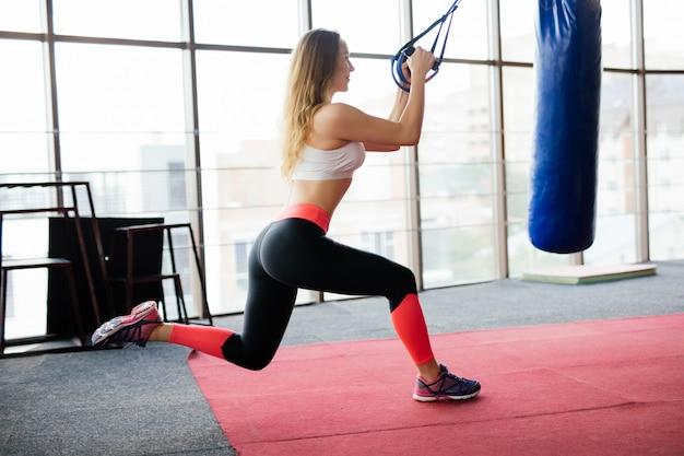 Kobieta fitness trening z paskami trx fitness w siłowni