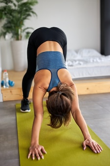 Kobieta fitness w dresie robi ćwiczenia na podłodze w studio, młoda kobieta zajmuje się sportem, prowadzi zdrowy tryb życia