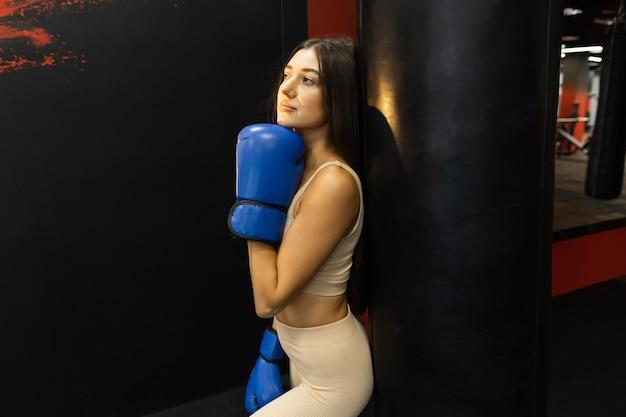 Kobieta fitness w niebieskich rękawicach bokserskich pozowanie