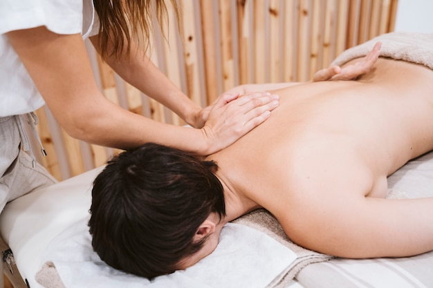Kobieta fizjoterapeuty daje masaż pleców do klienta w klinice