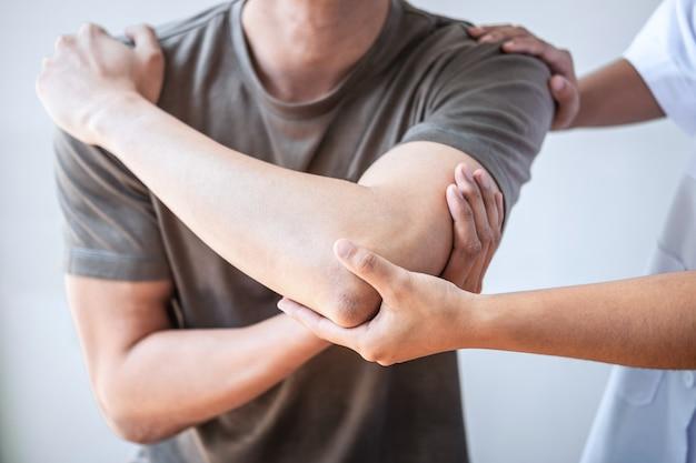 Kobieta fizjoterapeuty leczenia kontuzjowanego ramienia mężczyzny sportowca
