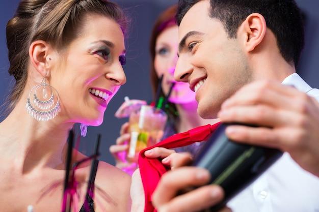 Kobieta flirtuje z barmanem w koktajl barze