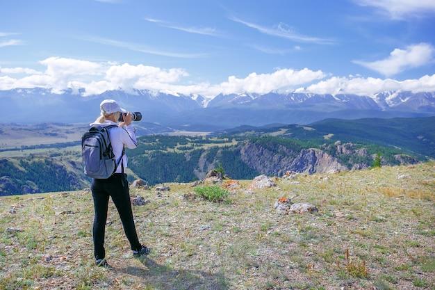 Kobieta fotograf bierze fotografię przy halnym szczytem. wycieczkowicz kobieta z plecakiem i kamerą robi fotografii na halnym szczycie.