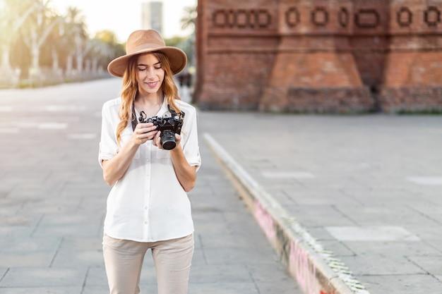Kobieta fotograf na zewnątrz przeglądanie zdjęć w aparacie.