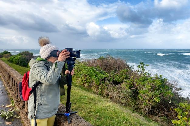 Kobieta fotograf pracuje podczas burzy w biarritz francja