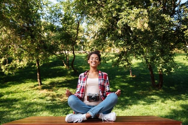 Kobieta fotograf siedzi na zewnątrz w parku medytować