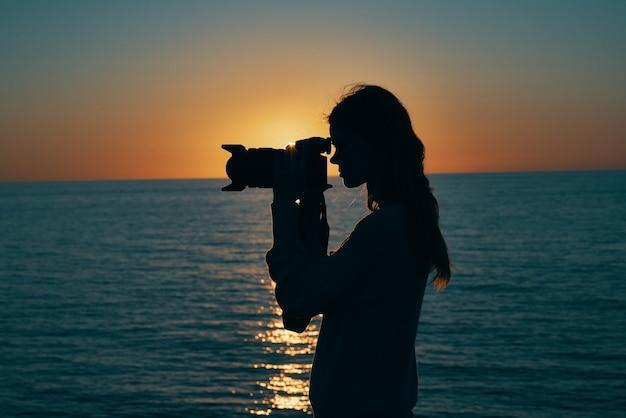Kobieta fotograf sylwetka o zachodzie słońca, w pobliżu widoku z boku na morze