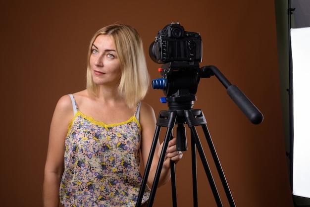 Kobieta fotograf z aparatem dslr w statywie w studio