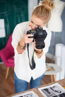 Kobieta fotografująca wydruki na stole