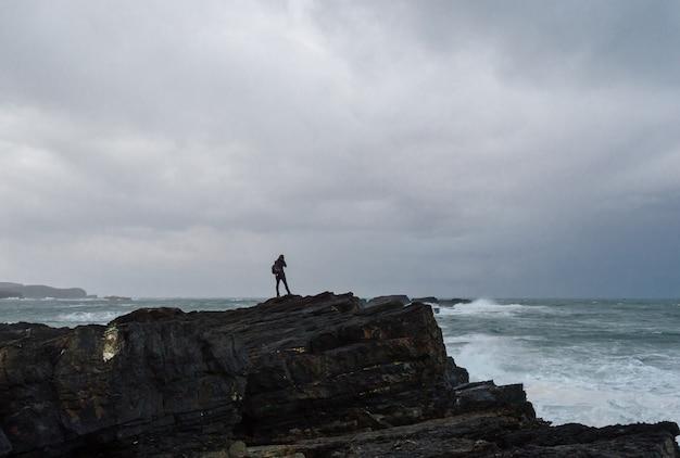 Kobieta fotografuje na krawędzi falezy przed burzą w cantabrian morzu.