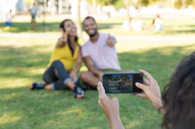 Kobieta fotografuje przyjaciół w parku
