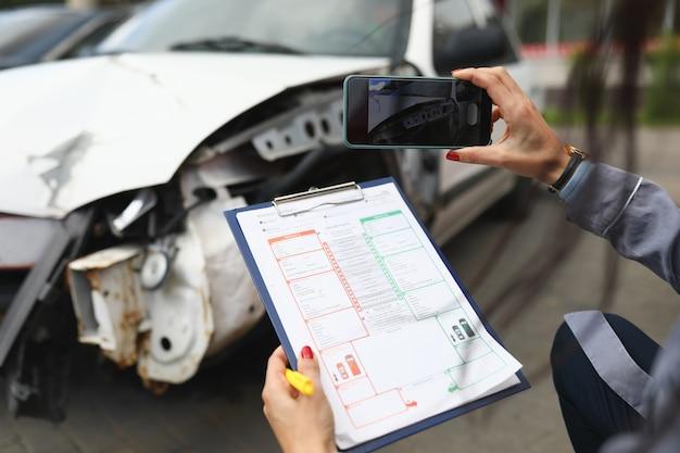 Kobieta fotografuje zepsuty samochód na smartfonie i posiada dokumenty ubezpieczeniowe