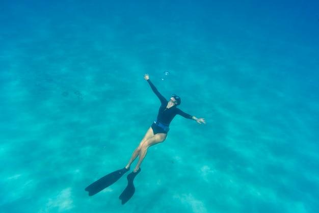 Kobieta freediving z płetwami pod wodą