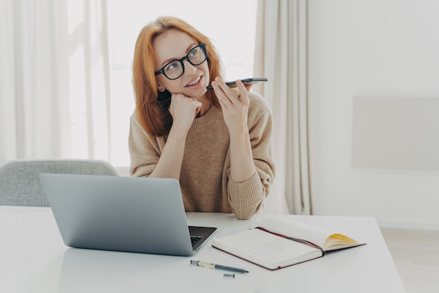 Kobieta freelancer nagrywa wiadomość głosową, siedzi na pulpicie, robi notatki w notatniku