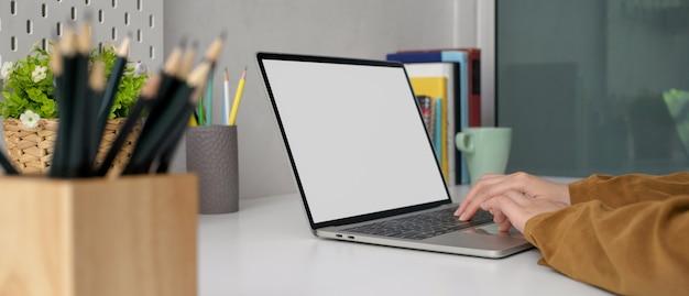 Kobieta freelancer pracuje w domu z laptopem z pustym ekranem na stylowym stole roboczym z książkami, artykułami biurowymi i dekoracjami