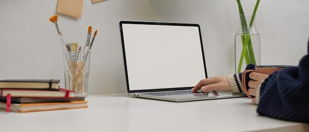 Kobieta freelancer wpisując na makiety laptopie trzymając kubek na białym biurku z dostawami w biurze domowym