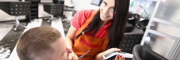 Kobieta fryzjer robi fryzurę mężczyźnie za pomocą nożyczek i maszynki do strzyżenia włosów