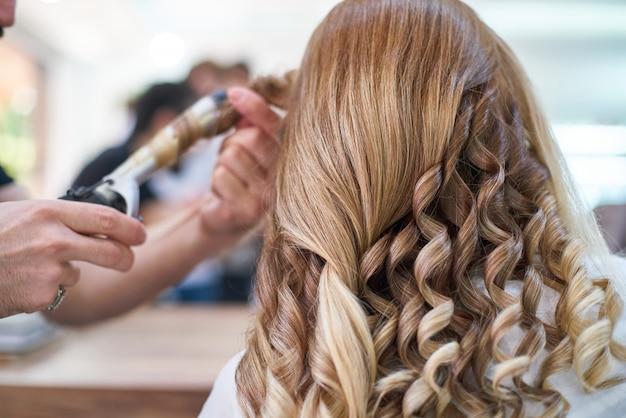 Kobieta fryzjer robi fryzurze w salonie piękności