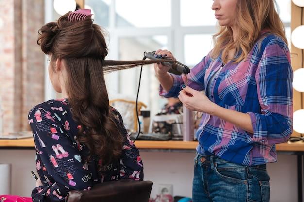 Kobieta fryzjer stojąca i używająca prostownicy do włosów na długie włosy młodej kobiety w salonie kosmetycznym