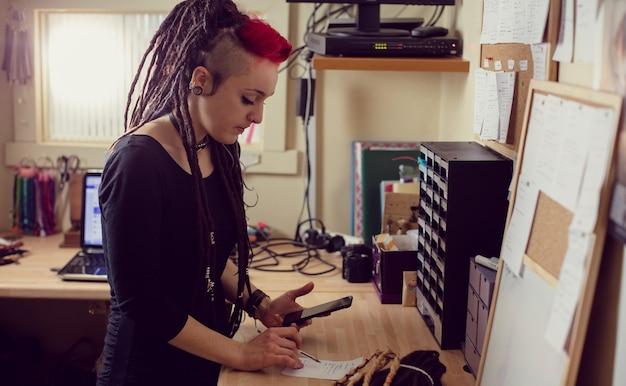 Kobieta fryzjer za pomocą telefonu komórkowego