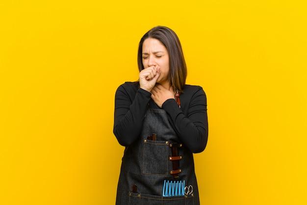 Kobieta fryzjerka mdłości z bólem gardła i objawami grypy, kaszel z zakrytymi ustami