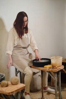 Kobieta garncarka pracująca na kole garncarskim w warsztacie