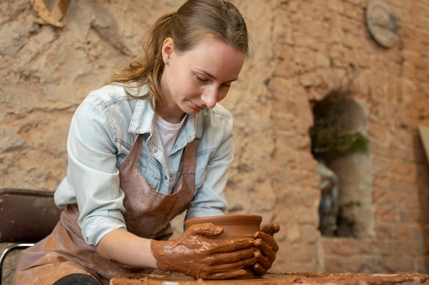 Kobieta garncarz pracująca na kole garncarskim wykonująca mistrza glinianego garnka, formującego glinę rękami tworząc garnek w warsztacie