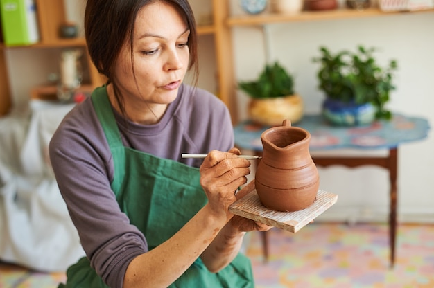 Kobieta garncarz robi dzbanek z gliny, rysuje wzór na produkcie.