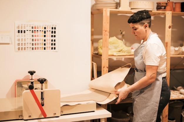 Kobieta garncarz w fartuchu spłaszcza glinę wewnątrz papieru za pomocą maszyny