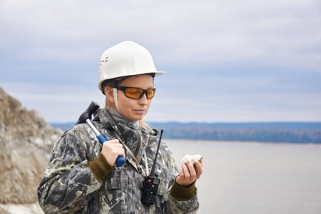 Kobieta geolog bada próbkę minerału na tle odkrywki na skraju góry