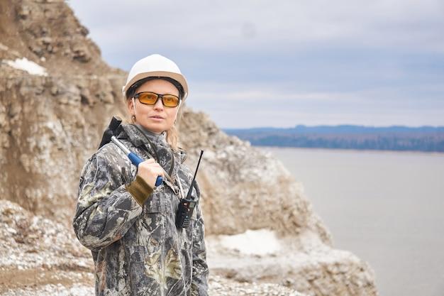 Kobieta geolog na tle odkrywki na skraju góry
