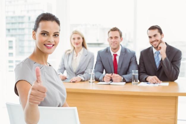 Kobieta gestykuluje aprobaty przed korporacyjnymi funkcjonariuszami personelu