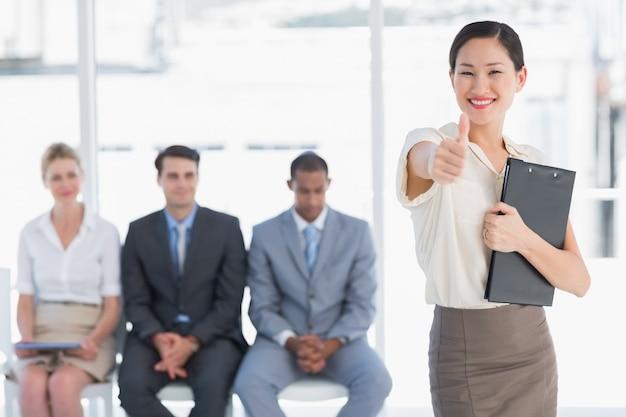 Kobieta gestykuluje aprobaty z ludźmi czeka wywiad