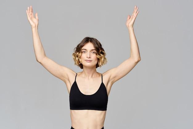 Kobieta gestykuluje rękami szczupła figura medytacja sport szary.