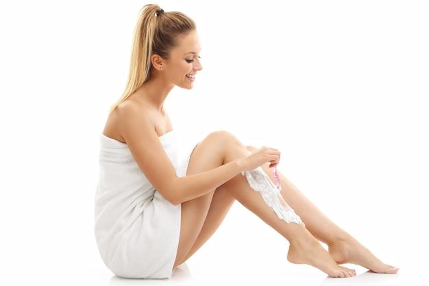 Kobieta goląca nogi na białym tle