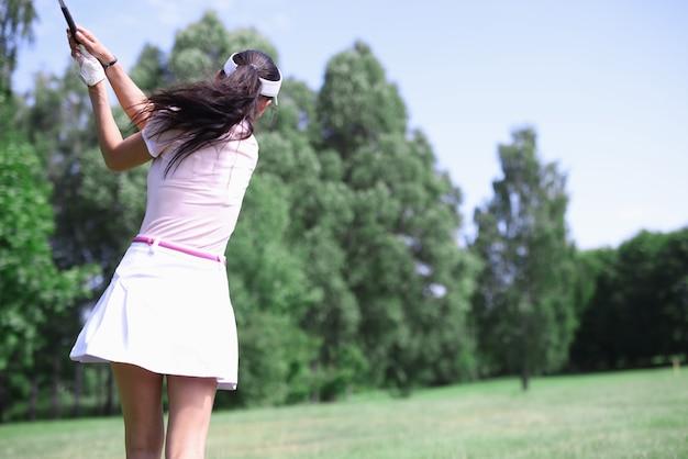 Kobieta golfista stoi plecami z kijem po uderzeniu.