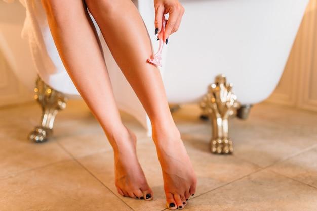 Kobieta goli nogi w łazience, pielęgnacji skóry. pielęgnacja ciała i higiena, opieka zdrowotna