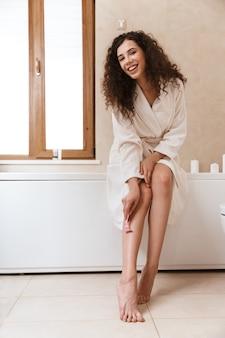 Kobieta goli nogi w łazience.